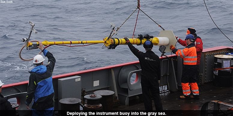 Deploying the instrument buoy into the gray sea.